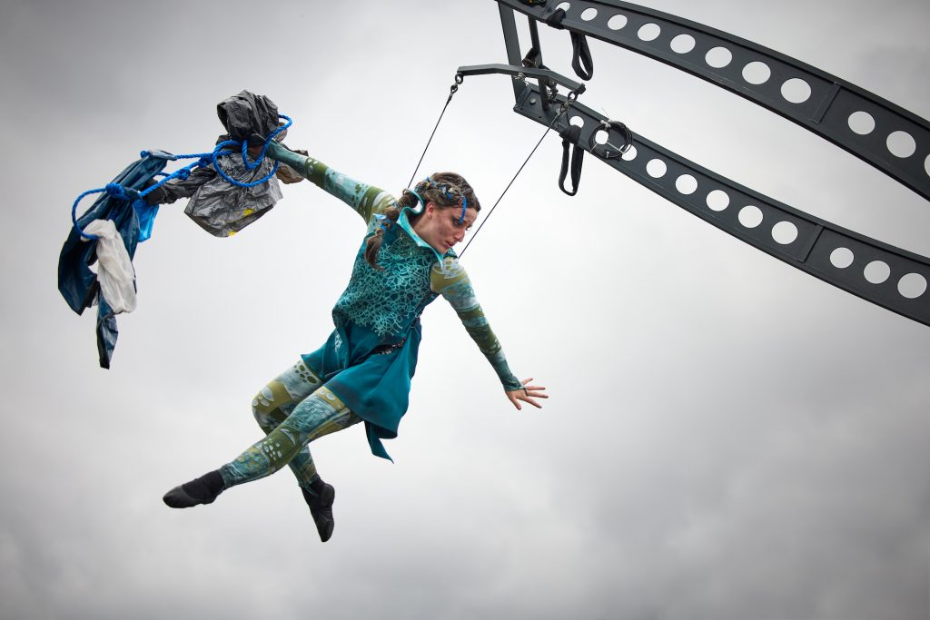 A performer in green hangs from an elevated platform in an aerial dance performance