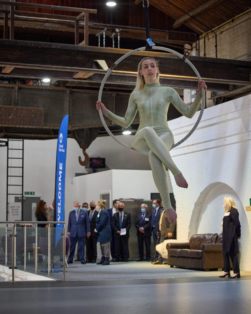 A woman sits in a hoop suspended from the ceiling. Her legs are crossed. She is wearing a silver catsuit. Behind her is a blue banner reading Welcome