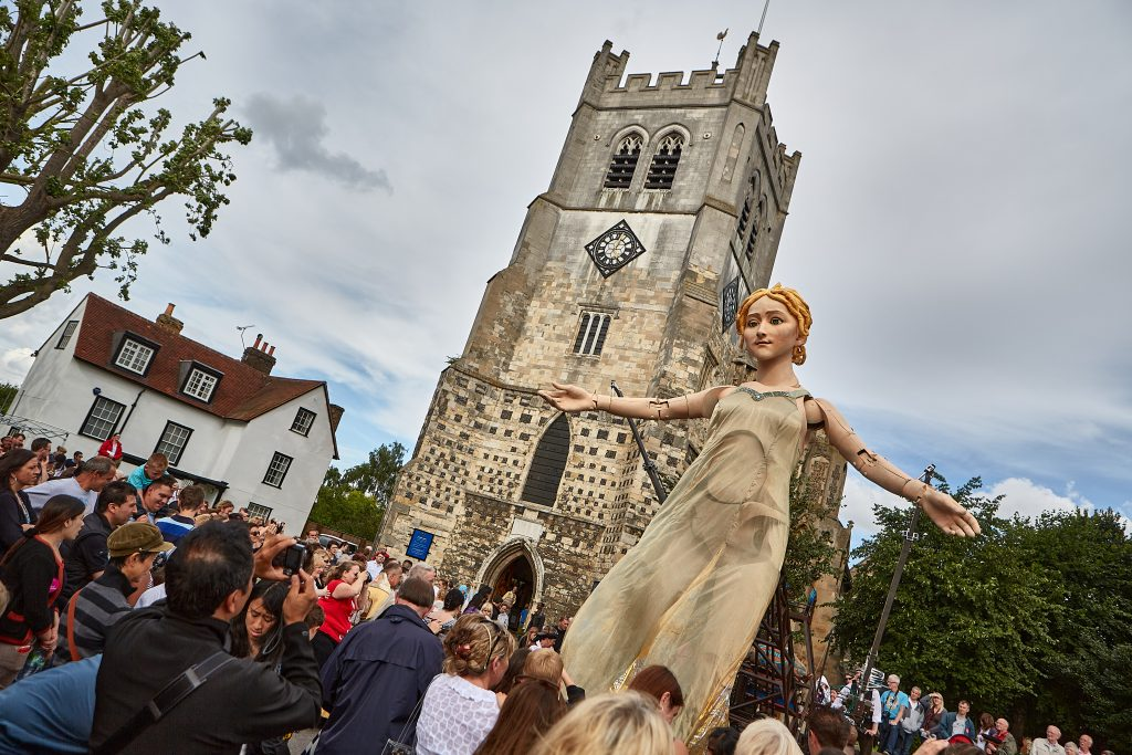 Godiva reaches out her arms to welcome the crowd. She is next to an ancient church , on her way from Hatfield and Waltham Abbey.