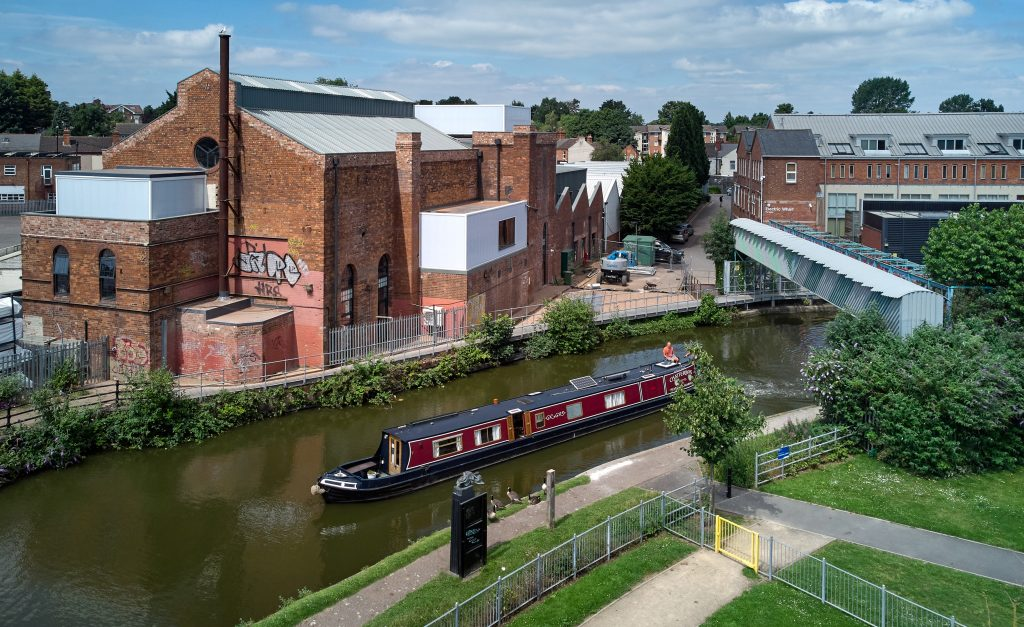 Aerial shot of The Daimler Powerhouse set against the canal, with a narrow boat in the foreground
